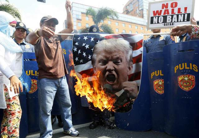 <p>Protesters burn a portrait of U.S. President Donald Trump during a rally at the U.S. Embassy to mark the Feb. 4, 1899, Filipino-American War, Feb. 4, 2017 in Manila, Philippines. (Photo: Bullit Marquez/AP) </p>