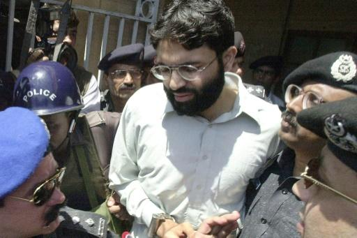 In this photo taken on March 29, 2002, Pakistani police surround a handcuffed Ahmed Omar Saeed Sheikh as he comes out of a court in Pakistan's port city of Karachi