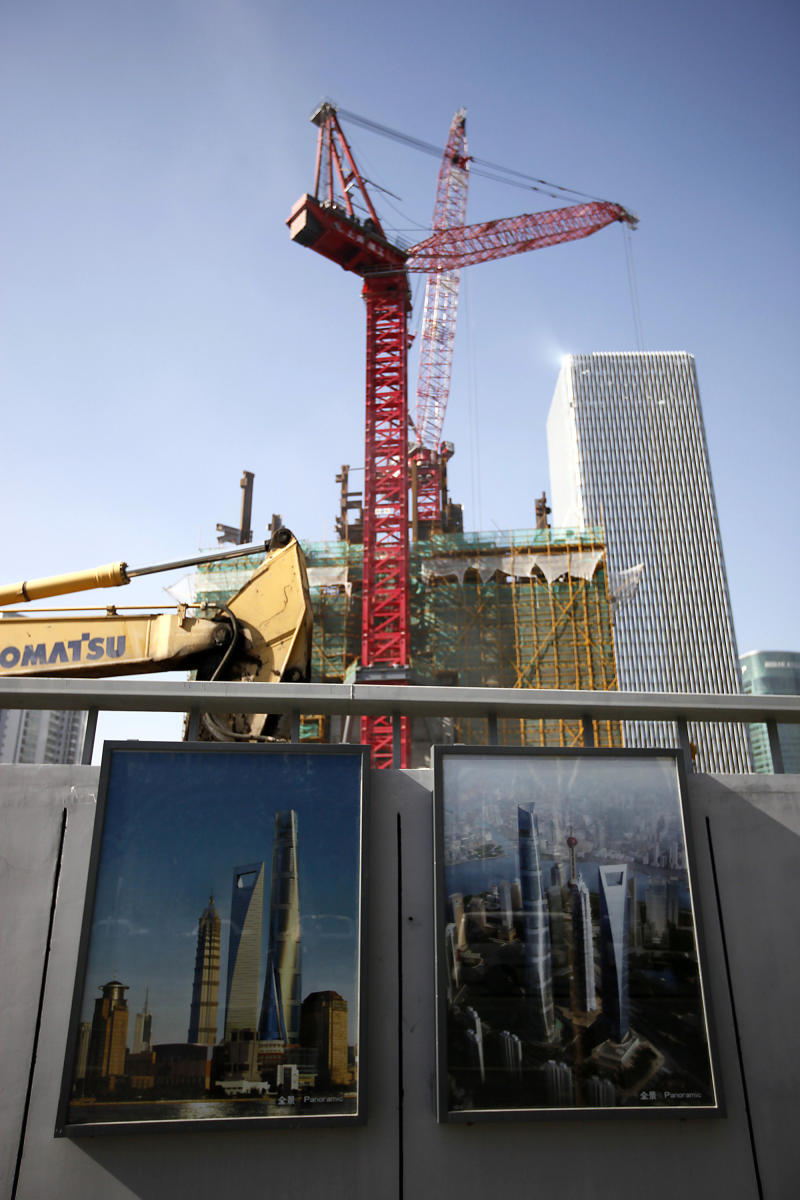 In this photo taken on Friday, Dec. 3, 2010, computer graphic illustrations of the Shanghai Tower are displayed outside its construction site in Shanghai, China. The 121-story Shanghai Tower is more than China's next record-setting building: It's an economic lifeline for the elite club of skyscraper builders.   (AP Photo/Eugene Hoshiko)