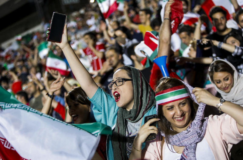 Iranian football supporters wave their national flags as they cheer for their national team during a screening of the Russia 2018 World Cup Group B football match between Iran and Spain in Azadi stadium in the capital Tehran on June 20, 2018. - Tehran's largest football stadium on June 20, 2018 admitted thousands of women together with men for the first time since the Islamic revolution of 1979 as World Cup fever gripped Iran for its evening group game against Spain. (Photo by STRINGER / AFP) / The erroneous mention[s] appearing in the metadata of this photo has been modified in AFP systems in the following manner: [STRINGER] instead of [ATTA KENARE]. Please immediately remove the erroneous mention[s] from all your online services and delete it (them) from your servers. If you have been authorized by AFP to distribute it (them) to third parties, please ensure that the same actions are carried out by them. Failure to promptly comply with these instructions will entail liability on your part for any continued or post notification usage. Therefore we thank you very much for all your attention and prompt action. We are sorry for the inconvenience this notification may cause and remain at your disposal for any further information you may require. (Photo credit should read STRINGER/AFP/Getty Images)