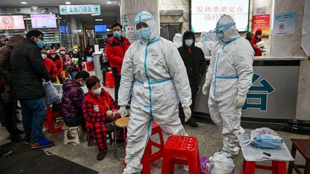 PHOTO: Medical staff members wearing protective clothing walk next to patients waiting for medical attention at the Wuhan Red Cross Hospital in Wuhan, China, Jan. 25, 2020. (Hector Retamal/AFP via Getty Images, FILE)
