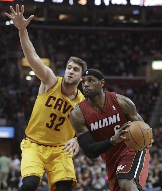 Miami Heat's LeBron James (6) drives around Cleveland Cavaliers' Spencer Hawes (32) during the first quarter of an NBA basketball game Tuesday, March 18, 2014, in Cleveland. (AP Photo/Tony Dejak)