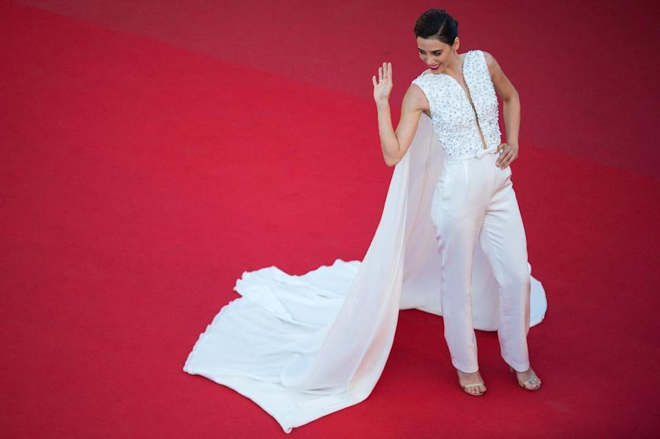 Cansu Dere paired white pants with a matching cape, guaranteeing she would not go unnoticed on the Croisette.