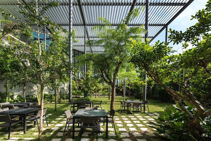 Outdoor tables and chairs in the factory let employees enjoy their lunch break surrounded by a sea of green.