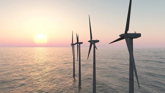 Offshore wind farm with a setting sun in the background.