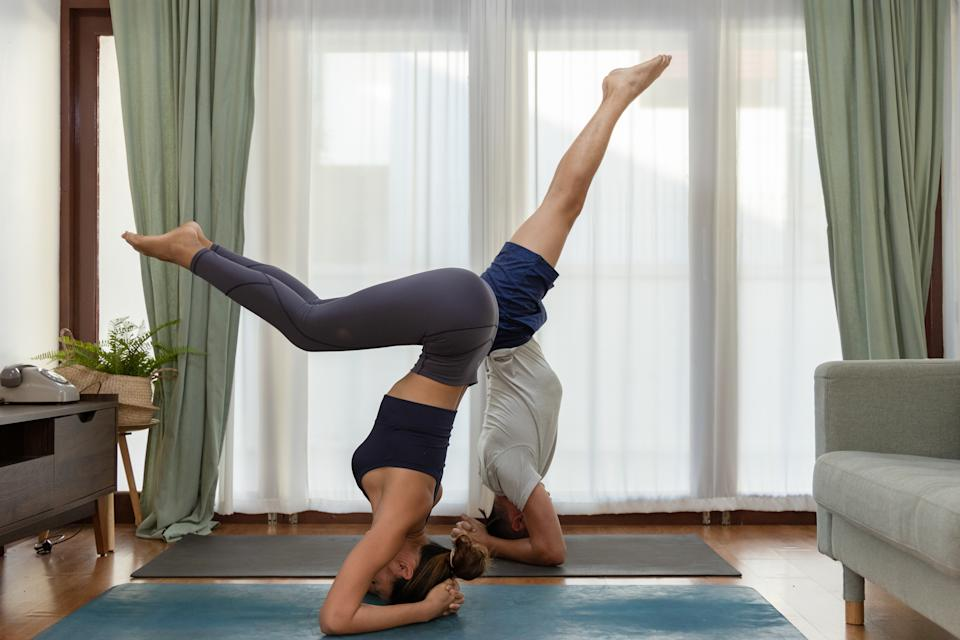 An Asian Couple practicing yoga together at home. They practice a variation of supported headstand posture.