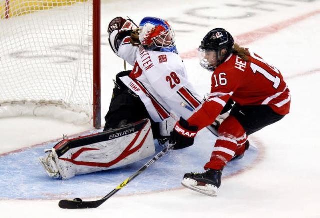 FILE PHOTO: Canada's Hefford scores on Switzerland's goalie Anthamatten as Switzerland's Bullo looks on during their preliminary round game at the IIHF Ice Hockey Women's World Championship in Ottawa