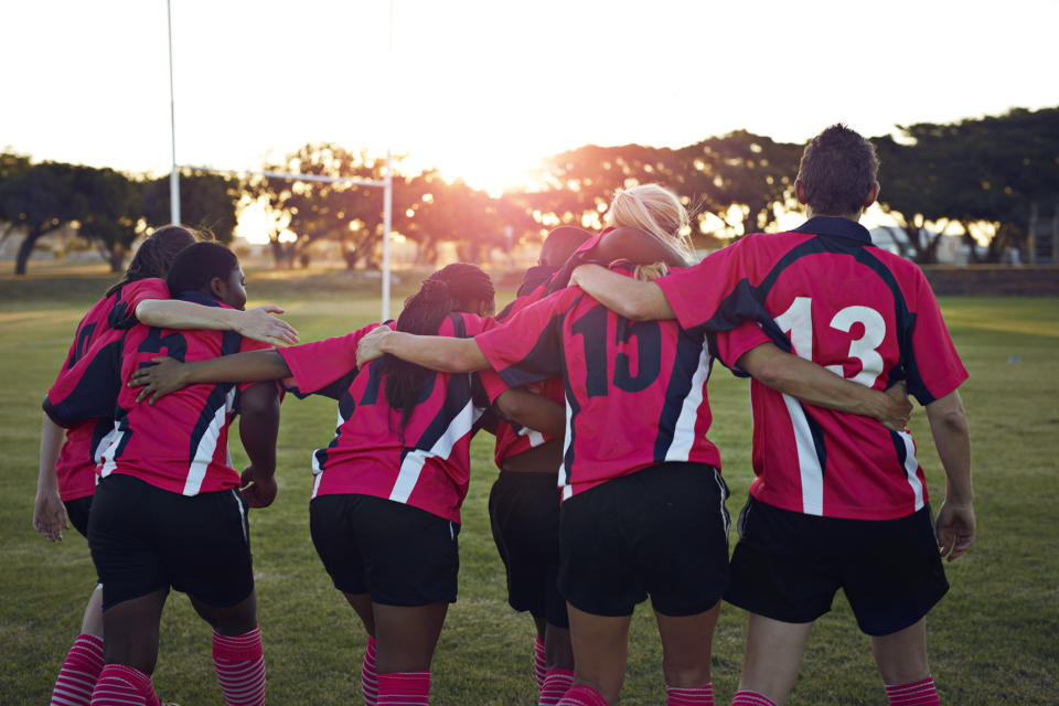 Women's rugby team walking together towards sunset.