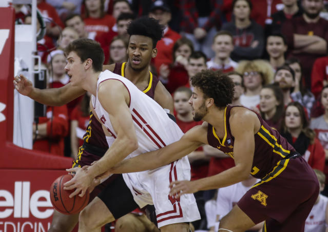 Wisconsin's Ethan Happ (22) drives against Minnesota's Eric Curry, behind, and Gabe Kalscheur, right, during the first half of an NCAA college basketball game Thursday, Jan. 3, 2019, in Madison, Wis. (AP Photo/Andy Manis)