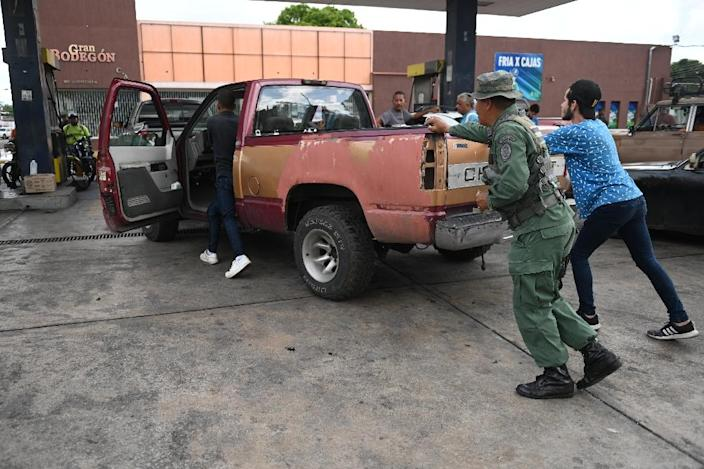 People push a vehicle up to the pump to fill up on gas at a station in Acarigua in Venezuela, which has started rationing fuel (AFP Photo/Marvin RECINOS)