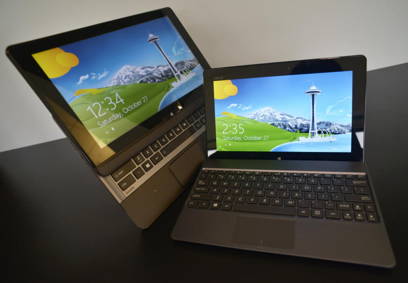 This Friday, Oct. 26, 2012 photo shows a partially-extended Toshiba U925t laptop-tablet computer, left, and the Asus Vivo Tab RT tablet computer docked to a keyboard in New York. (AP Photo/Patrick Sison)
