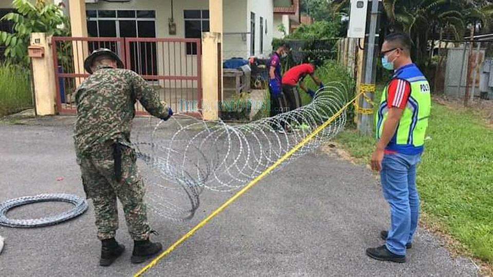 File picture shows the setting up of barbed wires to mark the EMCO areas in Bintulu. — Borneo Post Online pic
