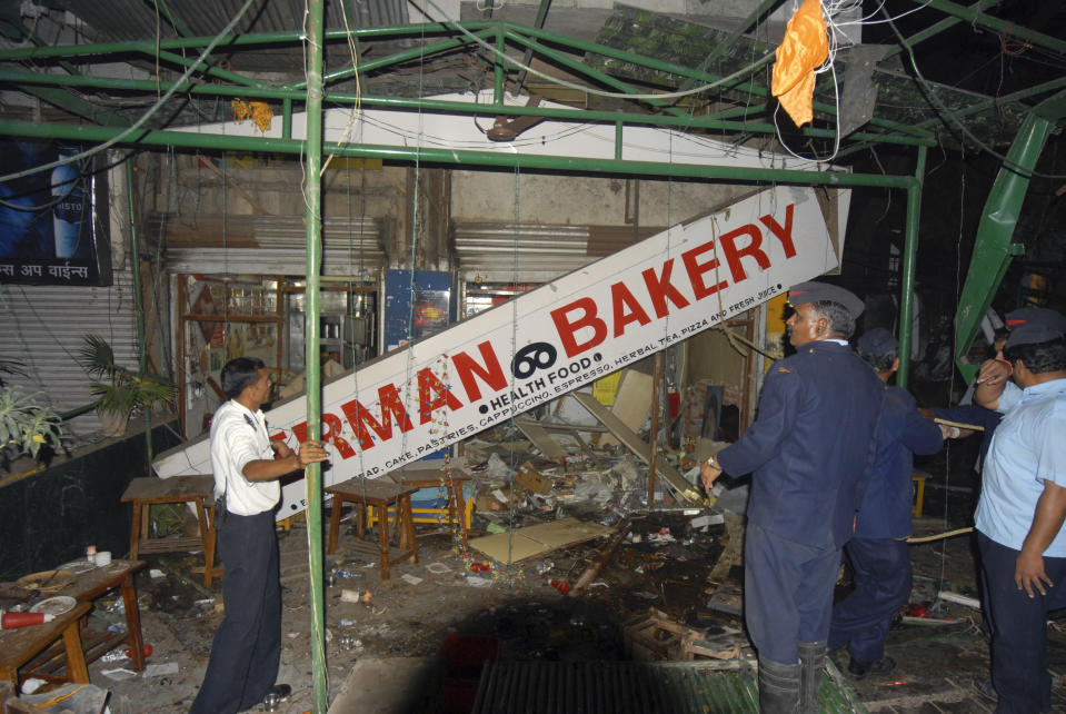 Indian police and rescue workers inspect the site of an explosion in German Bakery close to the Osho Ashram in Pune on. Feb. 13, 2010. (AP Photo)