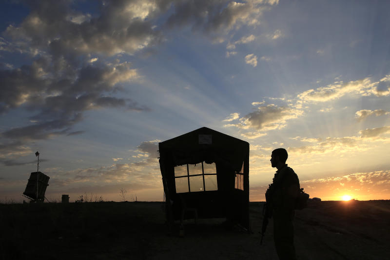 An Israeli soldier stands near an Iron Dome anti-missile battery system, on the far left, near the southern city of Sderot, Israel, Wednesday, Dec. 25. 2013, 2013. Israeli air and ground forces launched a series of attacks Tuesday on targets across the Gaza Strip, killing a young girl and wounding several in response to the deadly shooting of an Israeli civilian by a Palestinian sniper. (AP Photo/Tsafrir Abayov)