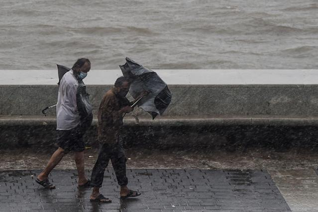 Two men carrying umbrellas walk on the Marine Drive under heavy rain in Mumbai on June 3, 2020. (Photo by PUNIT PARANJPE/AFP via Getty Images)