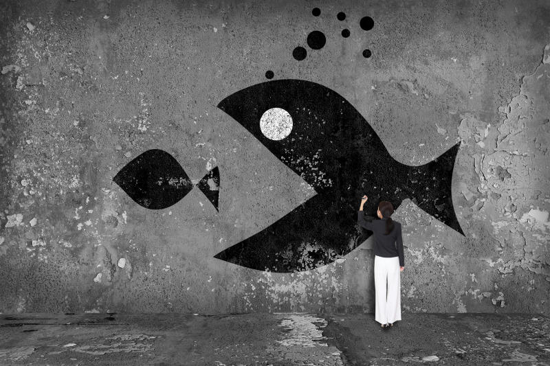 A person painting a picture of a big fish opening its mouth around a smaller fish.
