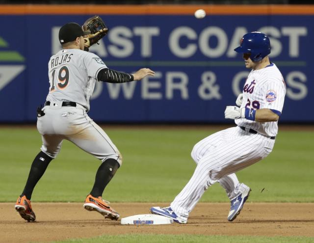 New York Mets' Devin Mesoraco (29) beats the throw to second base for a double as Miami Marlins shortstop Miguel Rojas (19) waits for the ball during the seventh inning of a baseball game Monday, May 21, 2018, in New York. (AP Photo/Frank Franklin II)