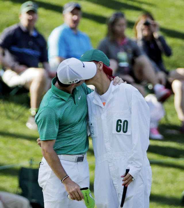 Rory McIlroy, of Northern Ireland, kisses his fiancee and tennis player Caroline Wozniacki after Wozniacki putted on the ninth hole during the par three competition at the Masters golf tournament Wednesday, April 9, 2014, in Augusta, Ga. (AP Photo/David J. Phillip)