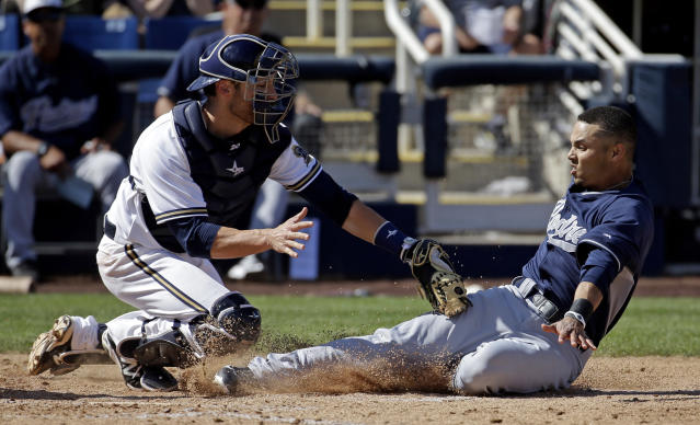 San Diego Padres' Rico Noel, right, slides safely past Milwaukee Brewers catcher Jonathan Lucroy for an inside-the-park home run during an exhibition spring training baseball game on Friday, March 7, 2014, in Phoenix. (AP Photo/Morry Gash)