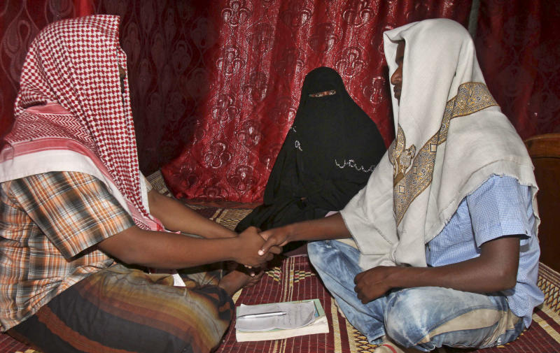 In this photo taken Wednesday, March 13, 2013, Abdi Ali, 25, right, shakes hands with an Islamic cleric who marries eloping couples, left, as Ali's girlfriend Anisa, 23, watches, during their elopement marriage in Walaweyn, Somalia. Since the Islamic extremist rebels of al-Shabab have been pushed out of almost all of Somalia's cities and towns, life has begun to return to normal, including elopements which al-Shabab under its strict interpretation of Islamic Shariah law had declared illegal and punishable by whipping or even death by stoning. (AP Photo/Farah Abdi Warsameh)