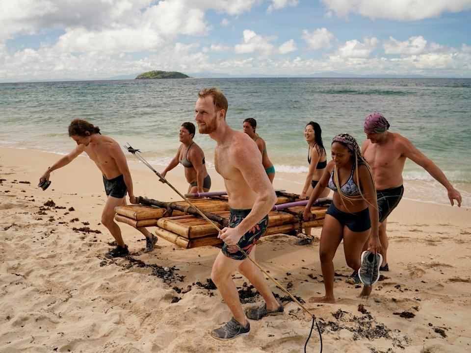 survivor players carrying a bamboo raft up the shore