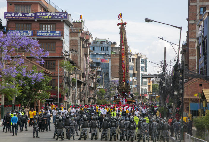 Policemen stand guard as Nepalese devotees pull a chariot during the Rato Machindranath chariot festival in Lalitpur, Nepal, Saturday, May 15, 2021. A truncated version of a Hindu chariot festival took place in Nepal's capital on Saturday amid strict COVID-19 restrictions, following an agreement between organizers and authorities that prevented a repeat of violent confrontations between police and protesters at last year's festival. (AP Photo/Niranjan Shrestha)