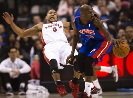 Toronto Raptors guard Jerryd Bayless, left, is knocked back by Detroit Pistons guard Walker Russell during first-half NBA basketball game action in Toronto, Wednesday, Feb. 22, 2012. (AP Photo/The Canadian Press, Nathan Denette)