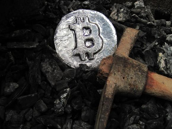 pickaxe and silver coin with bitcoin symbol on it lying on a pile of coal
