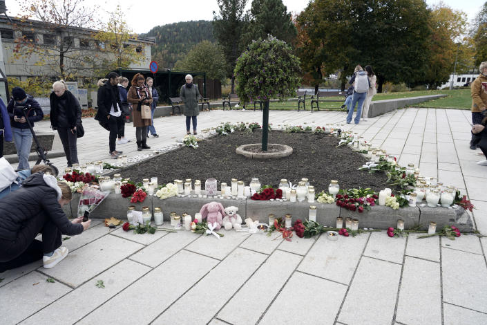 Flowers and candles are left after a man killed several people, in Kongsberg, Norway, Thursday, Oct. 14, 2021. Police in Norway are holding a 37-year-old man from Denmark suspected in a bow-and-arrow attack in a small town that killed five people and wounded two others. (Terje Pedersen/NTB via AP)