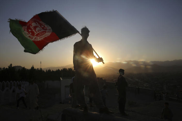 A man waves an Afghan flag during Independence Day celebrations in Kabul, Afghanistan, Monday, Aug. 19, 2019. Afghanistan's president is vowing to eliminate all safe havens of the Islamic State group as the country marks a subdued 100th Independence Day after a horrific wedding attack claimed by the local IS affiliate. (AP Photo/Rafiq Maqbool)