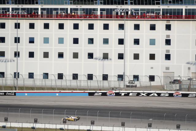 Fans on the patios of condos watch as race leader Josef Newgarden comes out of Turn 2 during an IndyCar auto race at Texas Motor Speedway in Fort Worth, Texas, Saturday, June 6, 2020. Condo residents were the only fans able to watch the race live. (AP Photo/Tony Gutierrez)