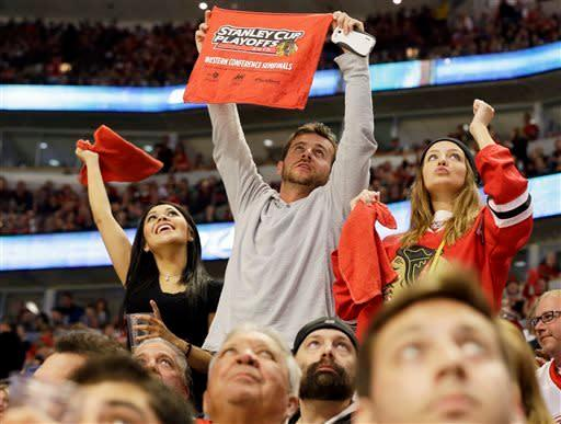 Chicago Blackhawks fans cheer for the team during the third period of Game 5 of the NHL hockey Stanley Cup playoffs Western Conference semifinals against the Detroit Red Wings in Chicago, Saturday, May 25, 2013. The Blackhawks won 4-1. (AP Photo/Nam Y. Huh)