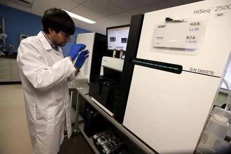 Technician Mike Lattari prepares a flow cell slide for loading onto a genetic sequencing machine at a Regeneron Pharmaceuticals Inc. laboratory at the biotechnology company's headquarters in Tarrytown, New York March 24, 2015. REUTERS/Mike Segar