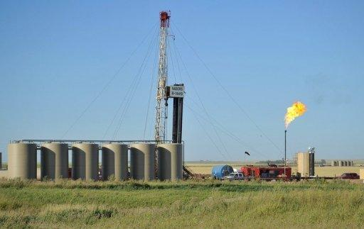 <p>Natural gas is burned off next to an oil well being drilled at a site August 23, 2011 near Tioga, North Dakota in the United States.</p>
