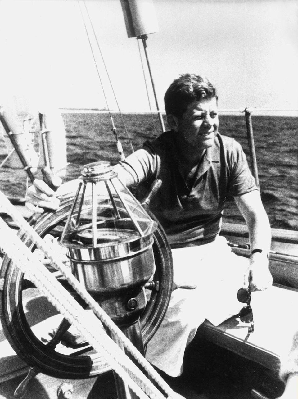 <p>John F. Kennedy steers a sailboat in 1961.</p>
