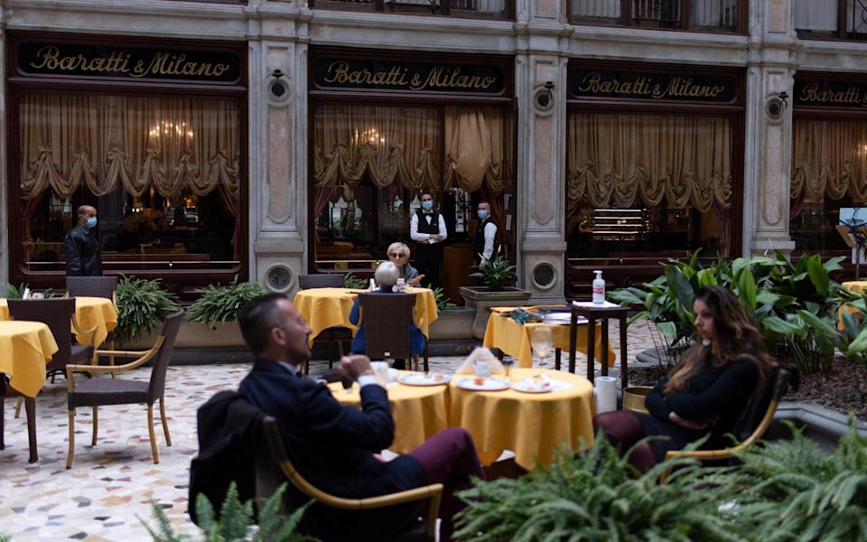 Patrons return to a reopened restaurant in Turin - Getty