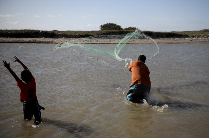 In this Aug. 2, 2019 photo, local tourists fish at in the waters of Playa Bagdad near the border city of Matamoros, Mexico. Besides fishing, contraband has always been here in one form or another: silver, or alcohol during Prohibition. In the 1980s and 90s, marijuana and Colombian cocaine. (AP Photo/Emilio Espejel)
