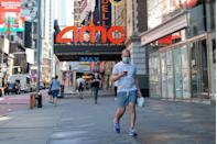 <p>man wearing a mask walks in front of an AMC movie theater in Times Square as the city continues Phase 4 of re-opening following restrictions imposed to slow the spread of coronavirus on August 20 in New York City.</p>