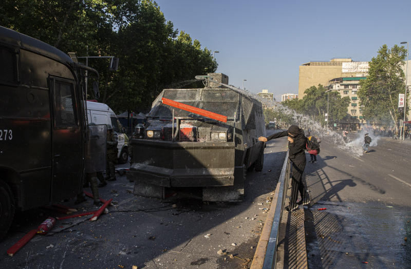 A protester throws a board at a water cannon during clashes with police in front of the Santa Lucia subway station during a protest against the rising cost of subway and bus fares, in Santiago, Friday, Oct. 18, 2019. (AP Photo/Esteban Felix)