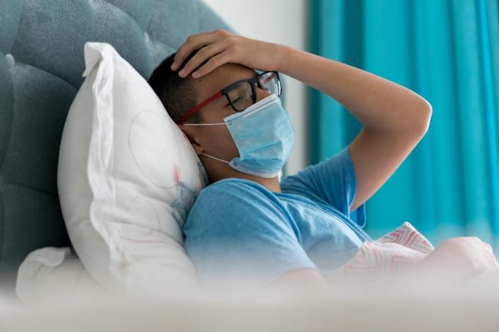 Teenage boy sick in bed with Covid-19 symptoms