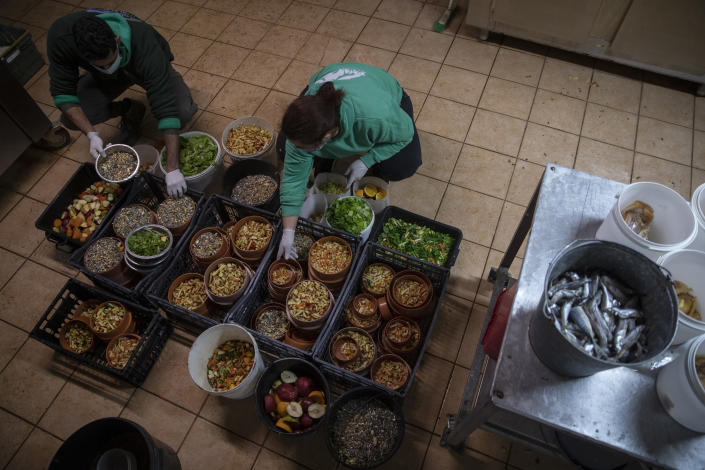 Zoo keepers Alexis left and Christina prepare food for the animals in the Attica Zoological Park in Spata, near Athens, on Tuesday, Jan. 26, 2021. (AP Photo/Petros Giannakouris)