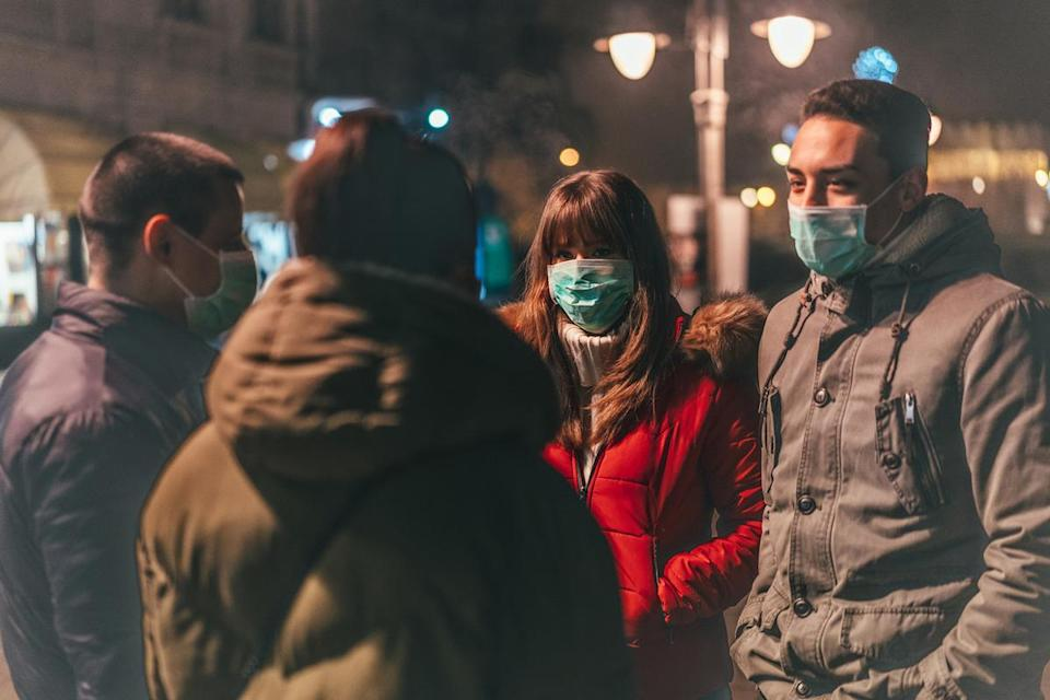 Group of young people with masks talking on street.