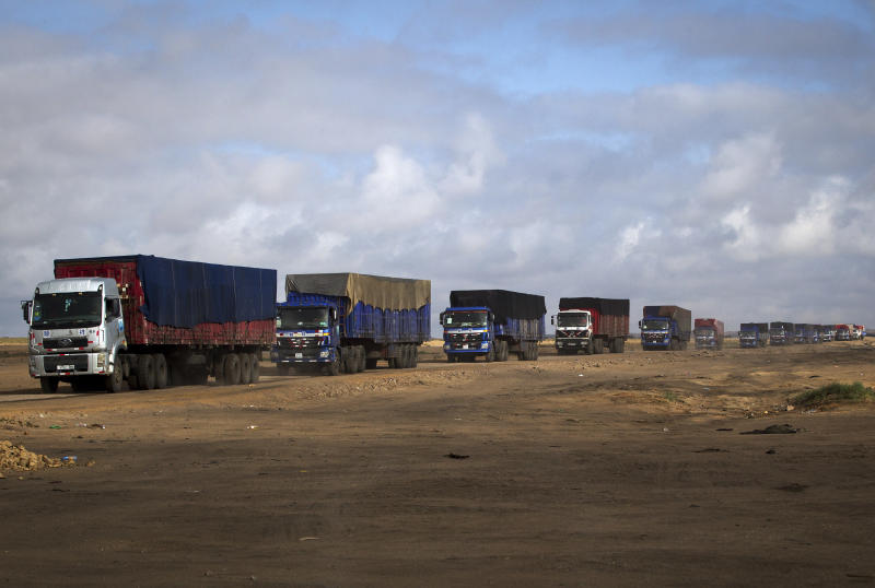 In this photo taken on July 7, 2012, trucks loaded with coking coal line up to enter a customs border between Mongolia and China near Tsogttsetsii, in southern Mongolia. Fully 90 percent of Mongolia's exports _ coal, copper, cashmere and livestock _ go to China, which in turn sends machinery, appliances and other consumer goods that account for a third of Mongolian imports. The rising trade with China now amounts to three-fourths of Mongolia's economy, one of the highest ratios in the world, according to an Associated Press analysis of IMF trade data. (AP Photo/Andy Wong)