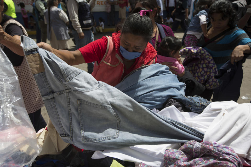 <p>A woman goes through a pile of donated clothes, outside a shelter in San Gregorio Atlapulco, Mexico, Friday, Sept. 22, 2017. Mexican officials are promising to keep up the search for survivors as rescue operations stretch into a fourth day following Tuesday's major earthquake that devastated Mexico City and nearby states. (AP Photo/Moises Castillo) </p>