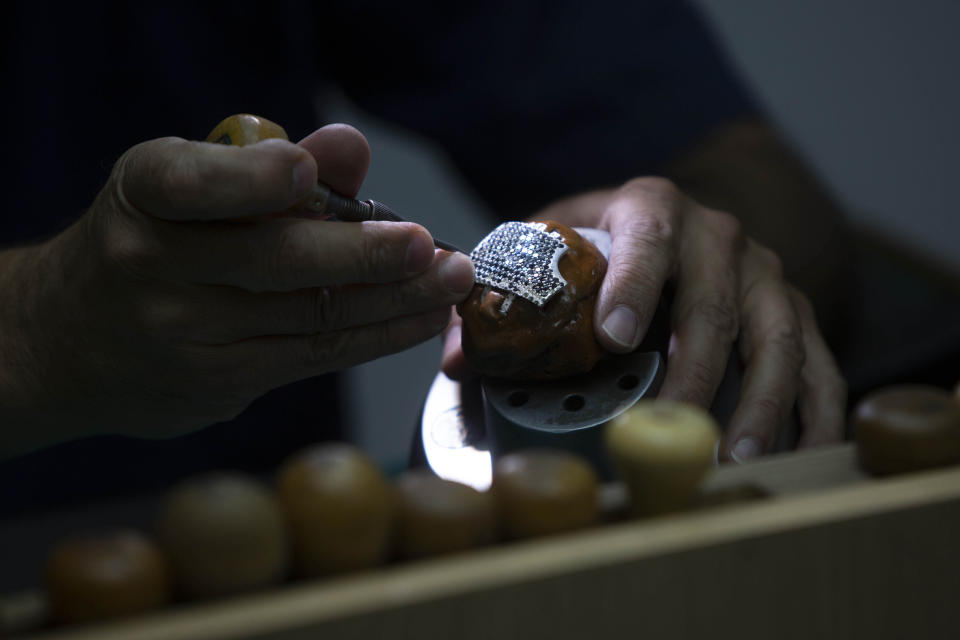 A worker for the Israeli jewelry company Yvel holds a part of a mask in Motza near Jerusalem, Sunday, Aug. 9, 2020. An Israeli jewelry company is working on what it says will be the world's most expensive coronavirus mask, a gold, diamond-encrusted face covering with a price tag of $1. 5 million. (AP Photo/Sebastian Scheiner)