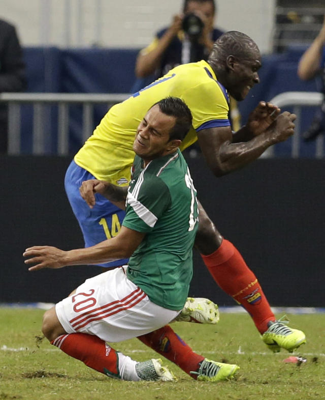 Mexico's Luis Montes collides with Ecuador's Segundo Castillo, rear, as the two were competing for the ball during the first half of a friendly soccer match, Saturday, May 31, 2014, in Arlington, Texas. Montes, who took the brunt of the collision was stretchered off the pitch after fracturing his right tibia and fibula. (AP Photo/Tony Gutierrez)