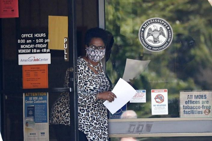 Worker wearing a mask to protect against coronavirus, holds an unemployment benefit application form as she waits for a client at the state WIN job center in Pearl, Miss. (AP Photo/Rogelio V. Solis, File)