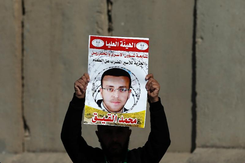 A Palestinian man carries a sign bearing a portrait of Palestinian journalist Mohammed al-Qiq, whose life is endangered after a 64-day-old hunger strike
