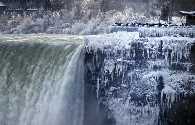 <p>Visitors take photographs at the brink of the Horseshoe Falls in Niagara Falls, Ont., Tuesday, Jan. 2, 2018. (Photo: Aaron Lynett/The Canadian Press via AP) </p>