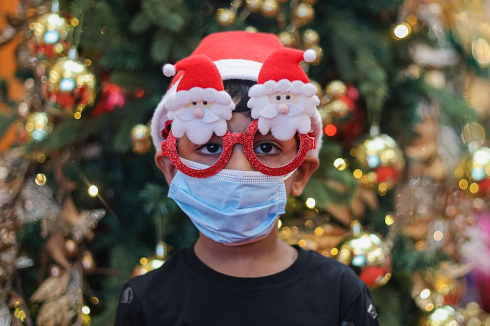 A boy wearing a face mask and Christmas decorative eye glasses at a shopping mall, amid the coronavirus crisis. (Photo by Annice Lyn / SOPA Images/Sipa USA)